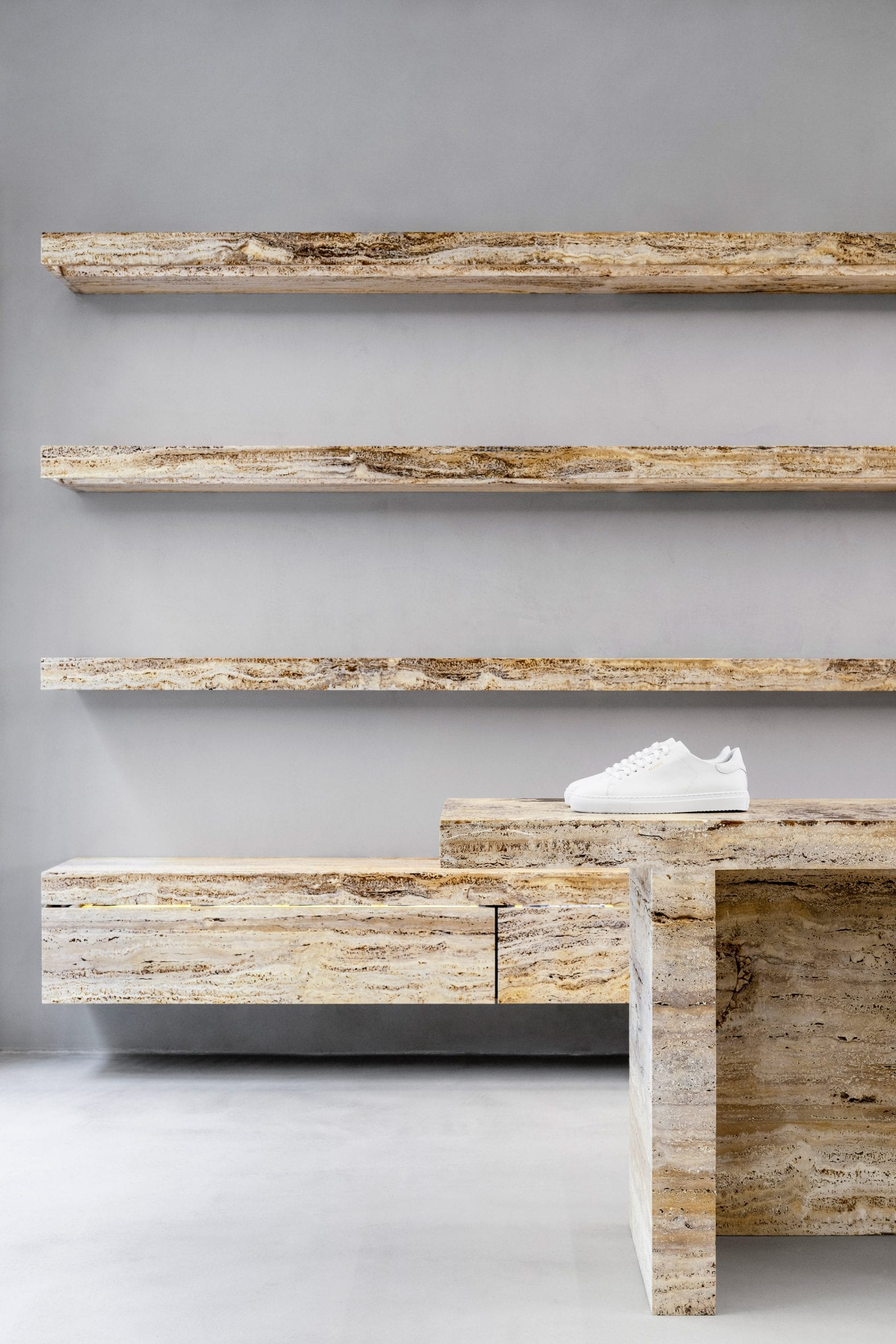 White sneaker on travertine shelves in retail interior by Halleroed