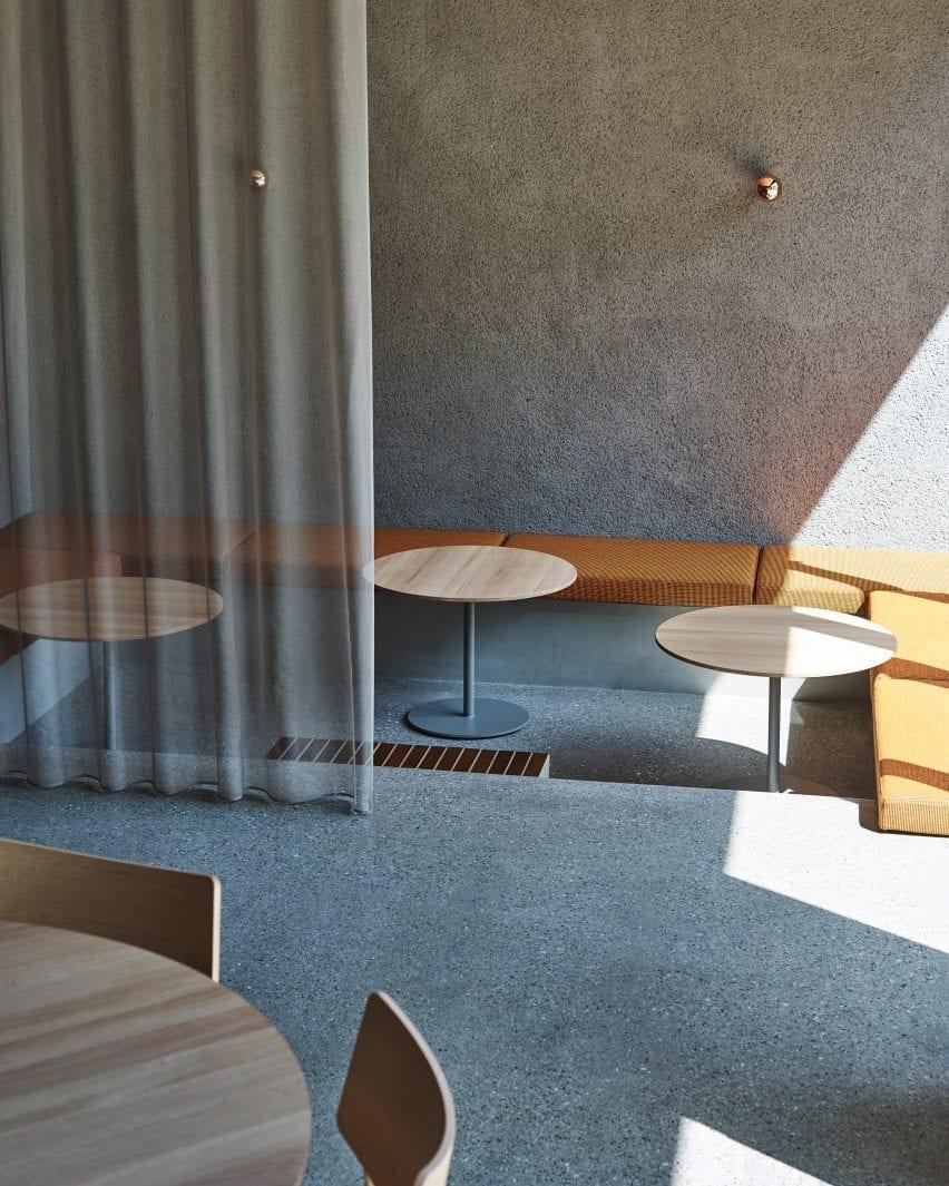A recessed seating area with orange cushions in the Keiji Ashizawa Design coffee shop