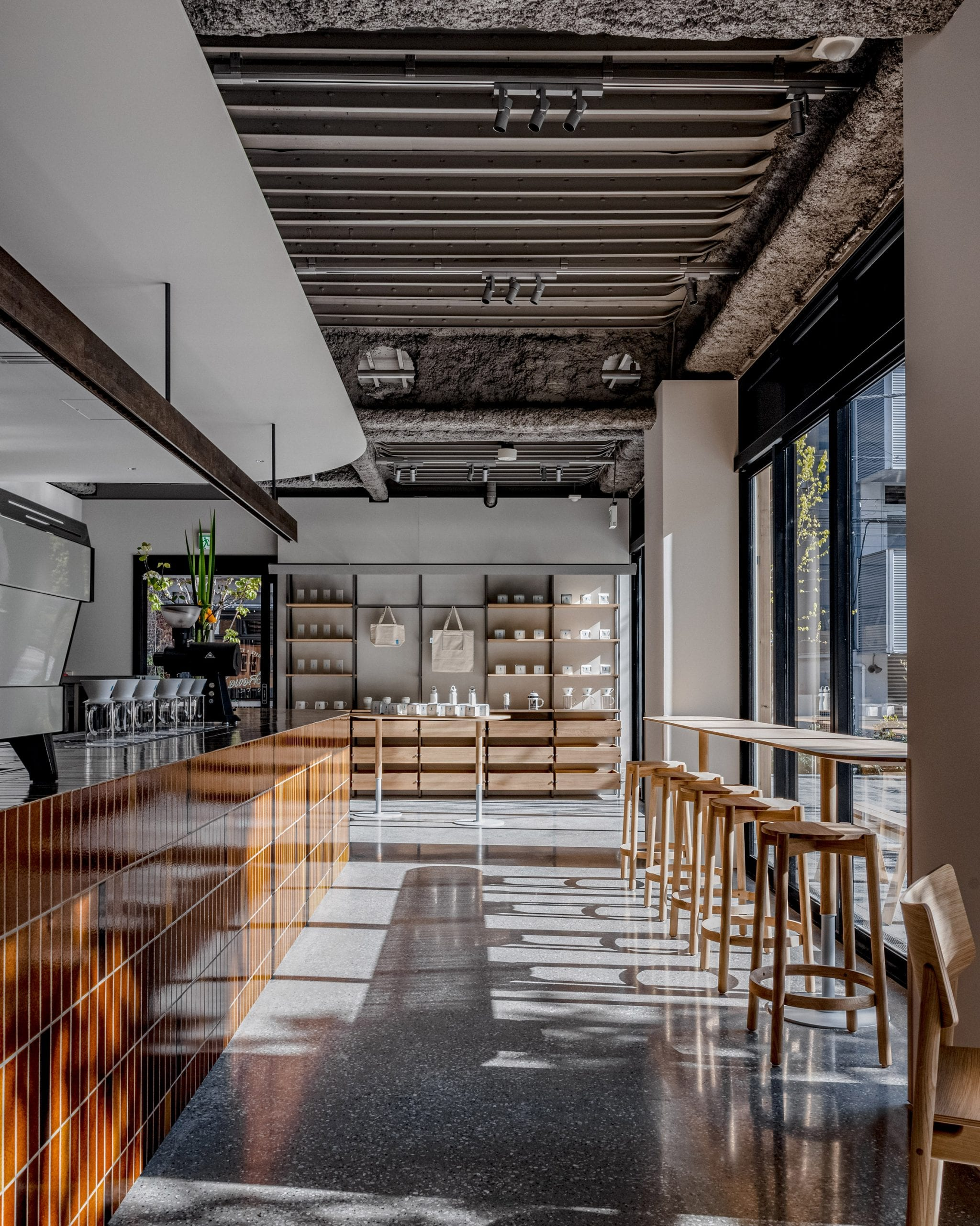 Brown-tiled bar and wooden counter seating in coffee shop by Keiji Ashizawa Design