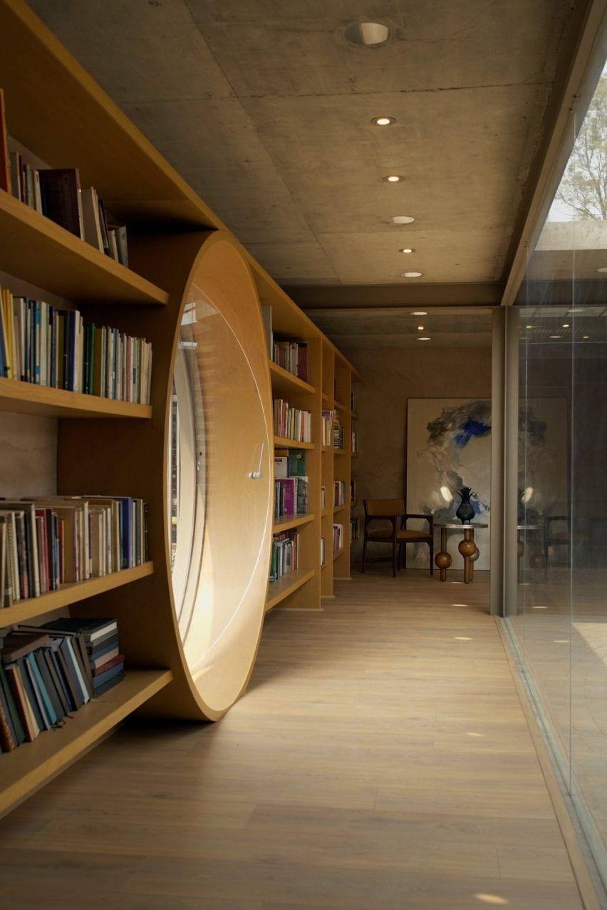 Puerta redonda de vidrio entre estanterías en Casa UC por Daniela Bosio Cestos