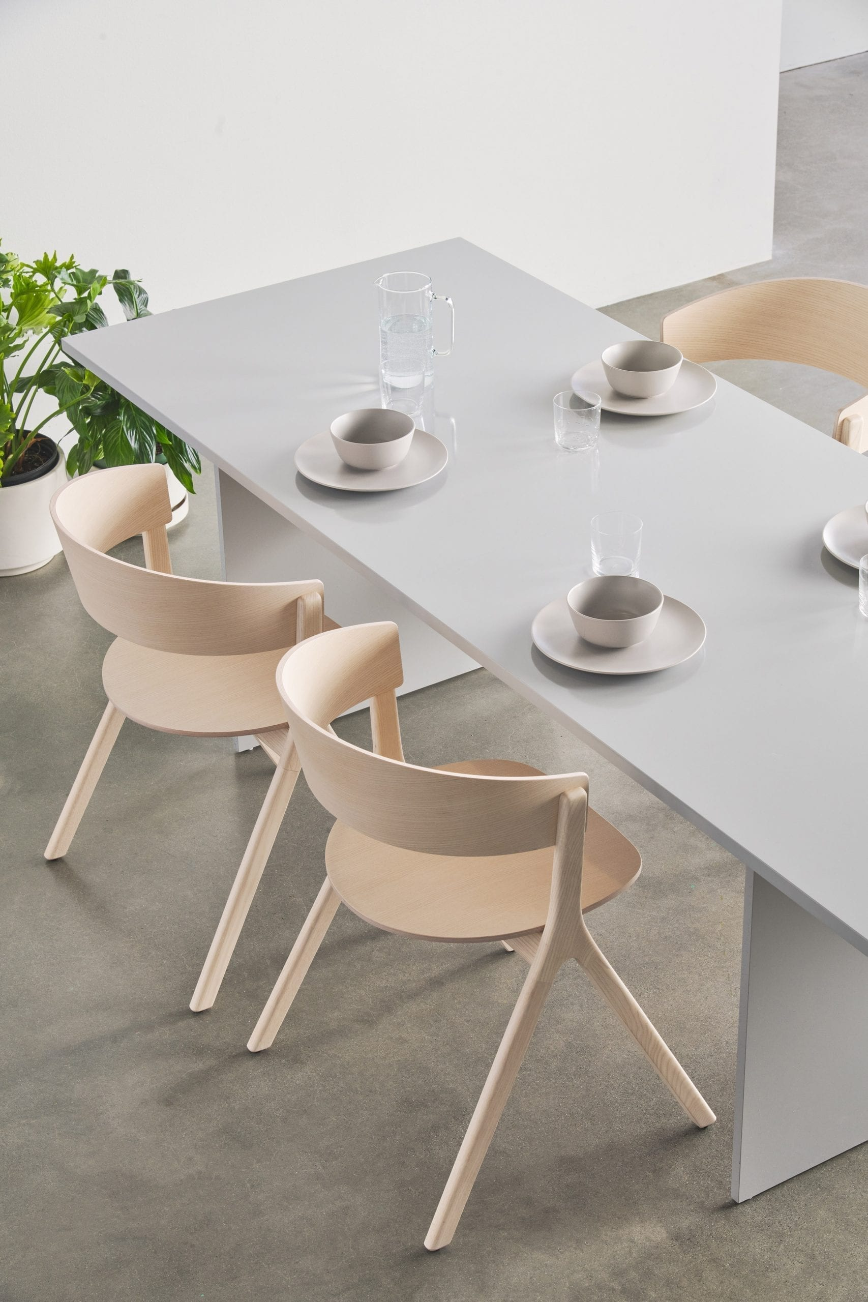 Wooden chairs around a grey table