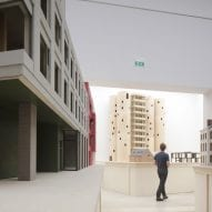 A visitor walking among architectural models