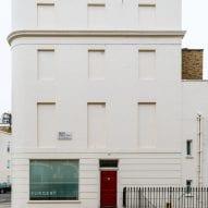 A windowless white facade of London housing