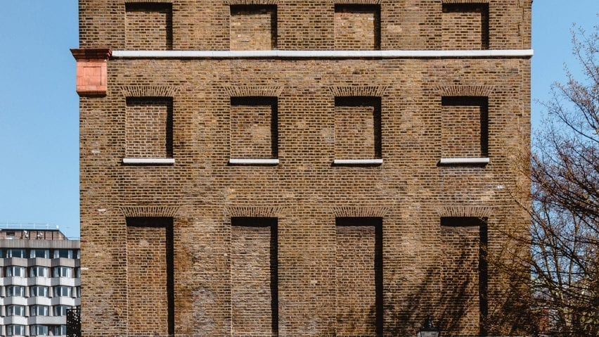 A brick facade with covered window areas