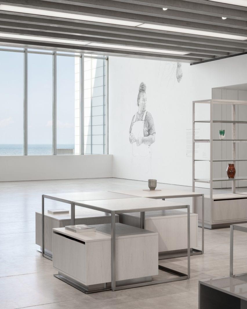 Loja com vista panorâmica do mar e vasos em prateleiras em interior projetado pela Daytrip