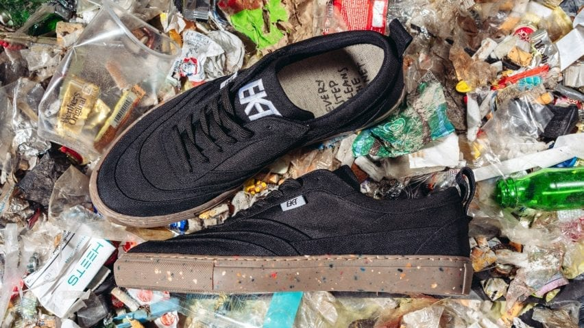 A pair of black trainers photographed on rubbish