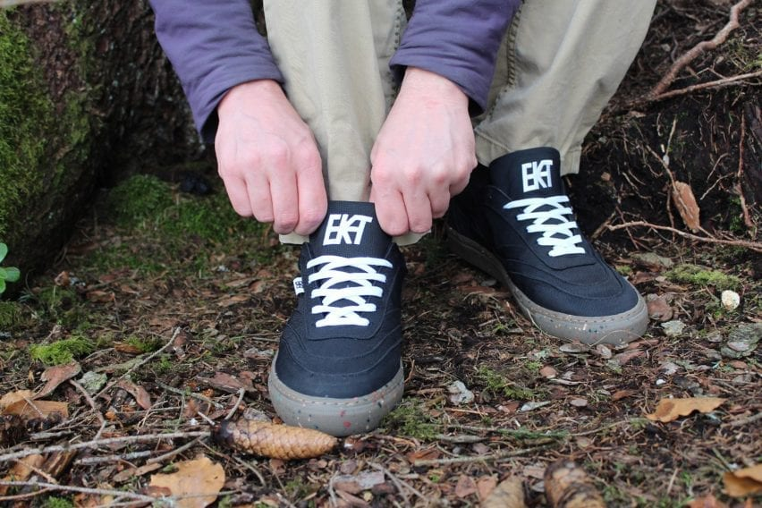 A wearer puts on a black pair of trainers