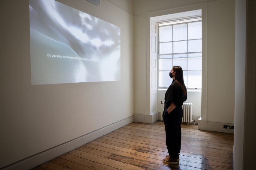 The artist is pictured watching a projection on a wall
