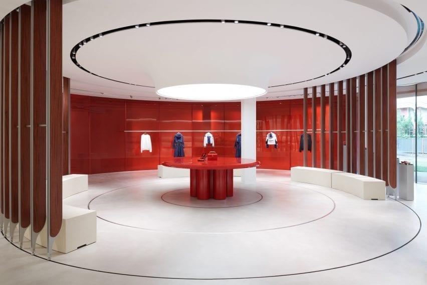 Rak pajangan dikelilingi oleh dinding kaca merah di interior toko oleh Sybarite