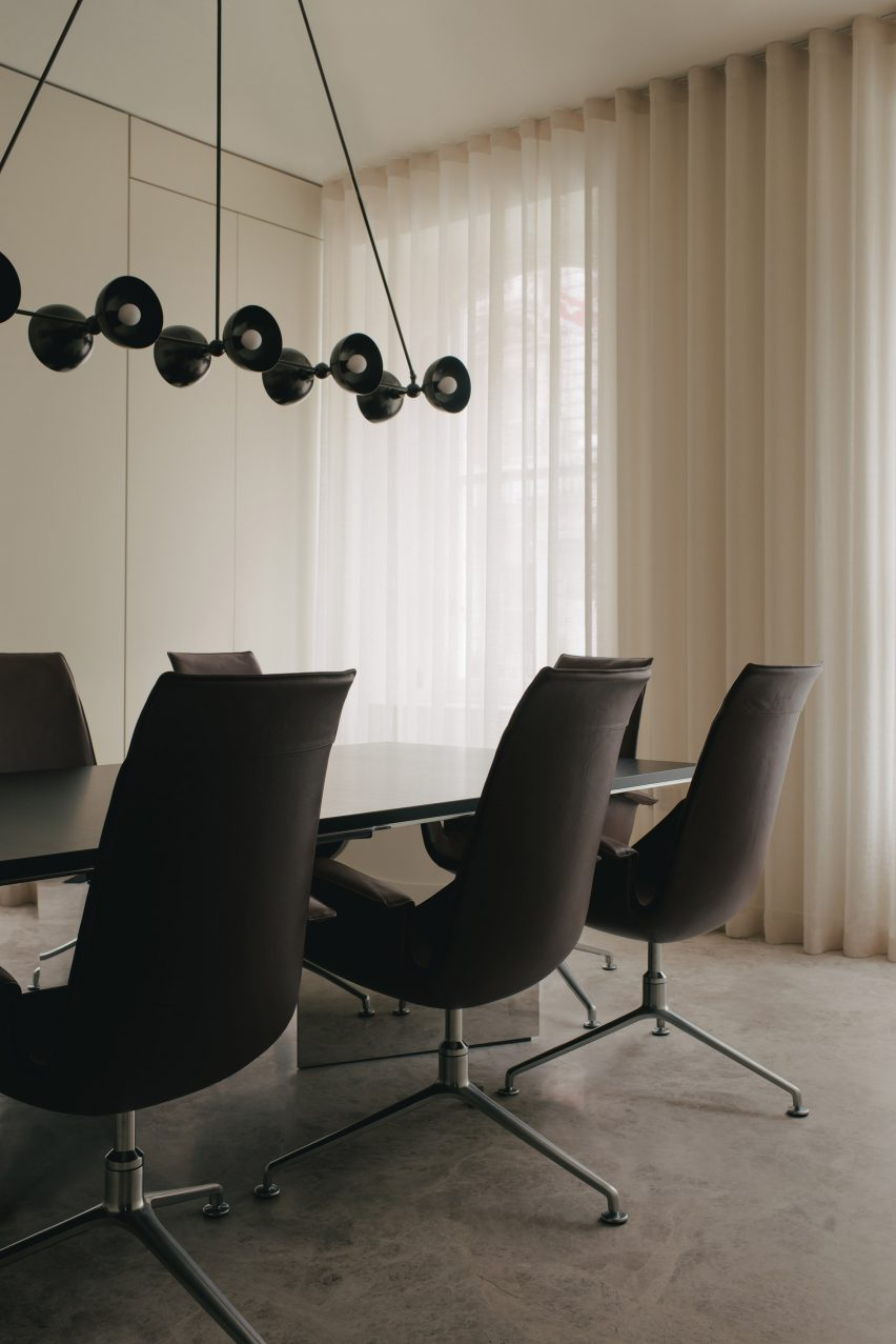 Meeting room with black chairs and large hanging lamp in Mandeville Place office