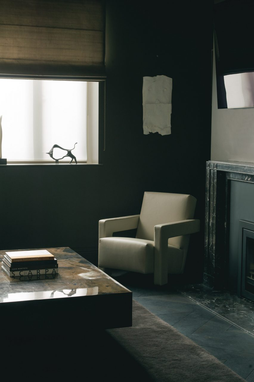 White armchair in a dark room with a stone table and fireplace in the London office of Hollie Bowden