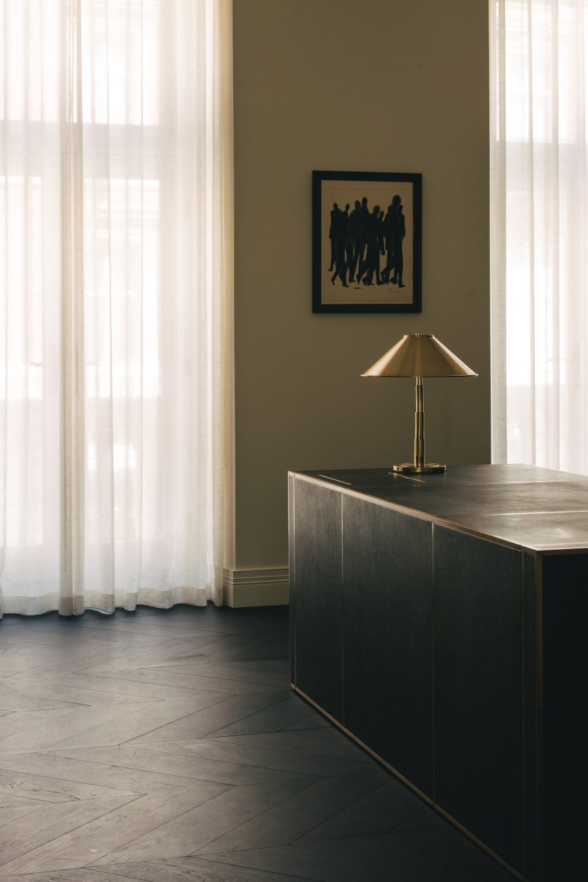 A black desk with a gold lamp in the Mandeville Place office
