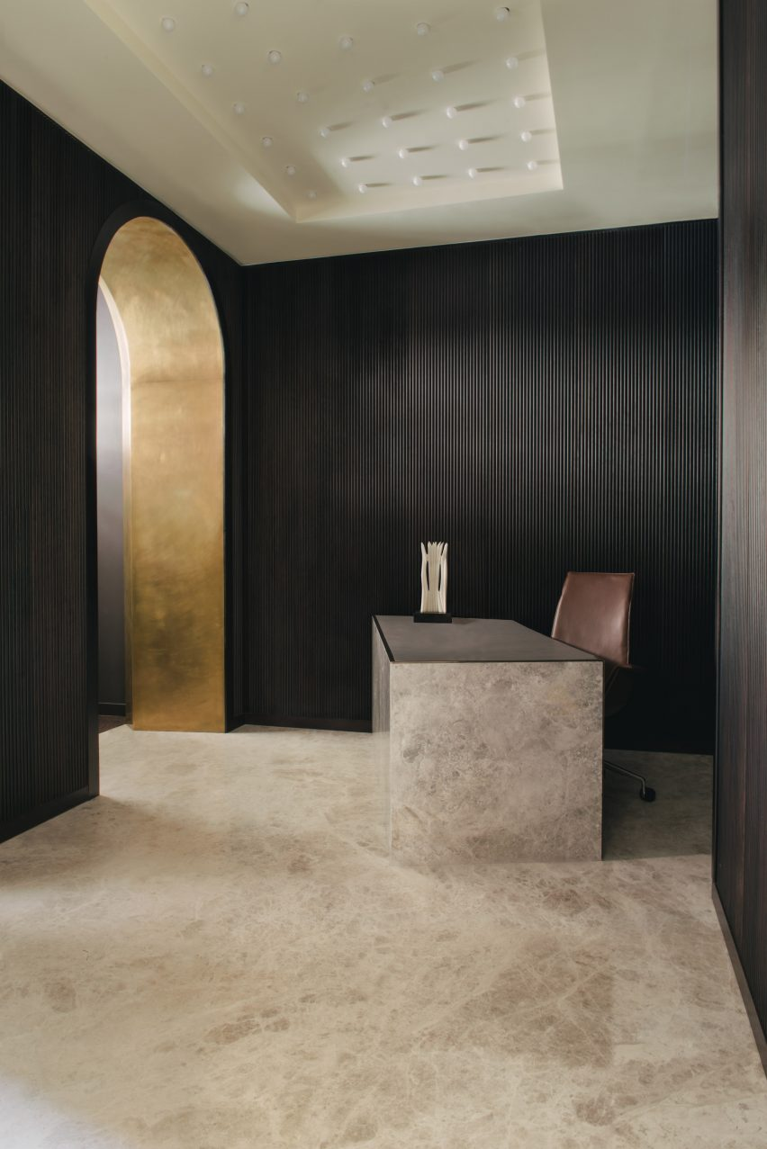 Lobby of Mandeville Place office with textured black walls, marble flooring and gold entryway