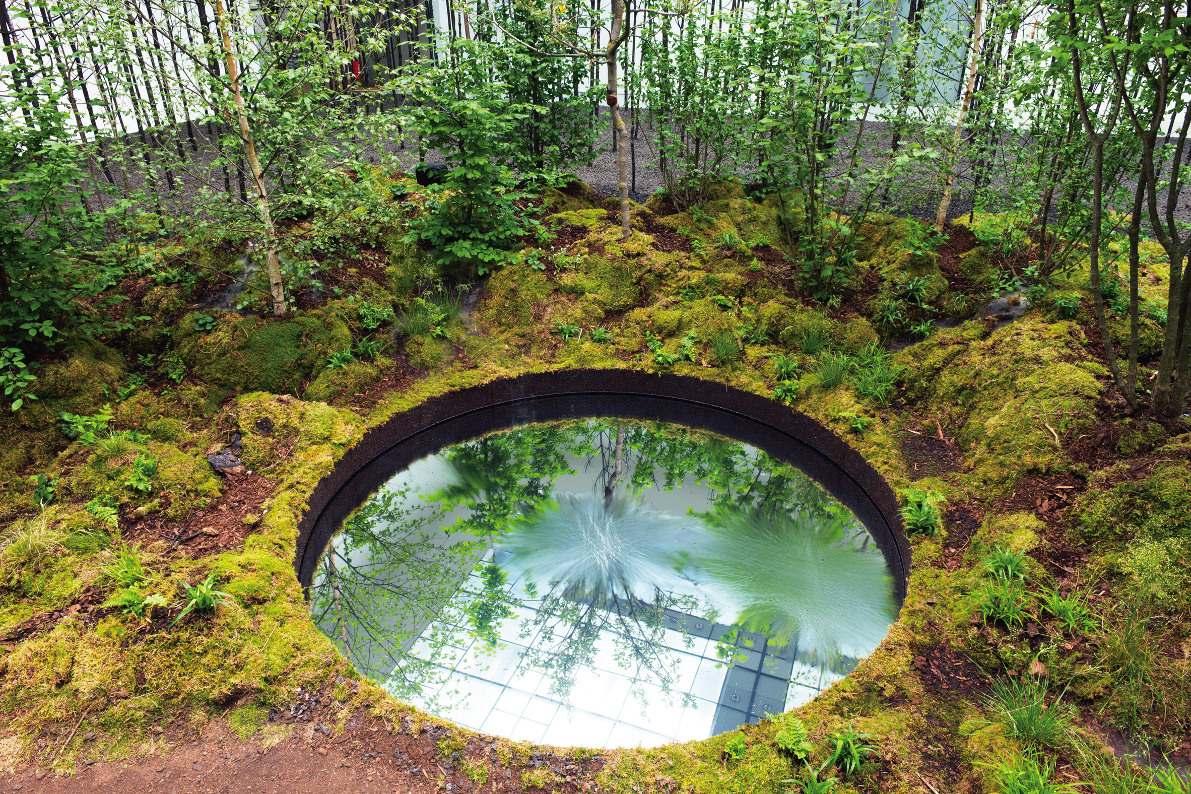 Invocation for Hope in Vienna features a circular reflection pool surrounded by moss