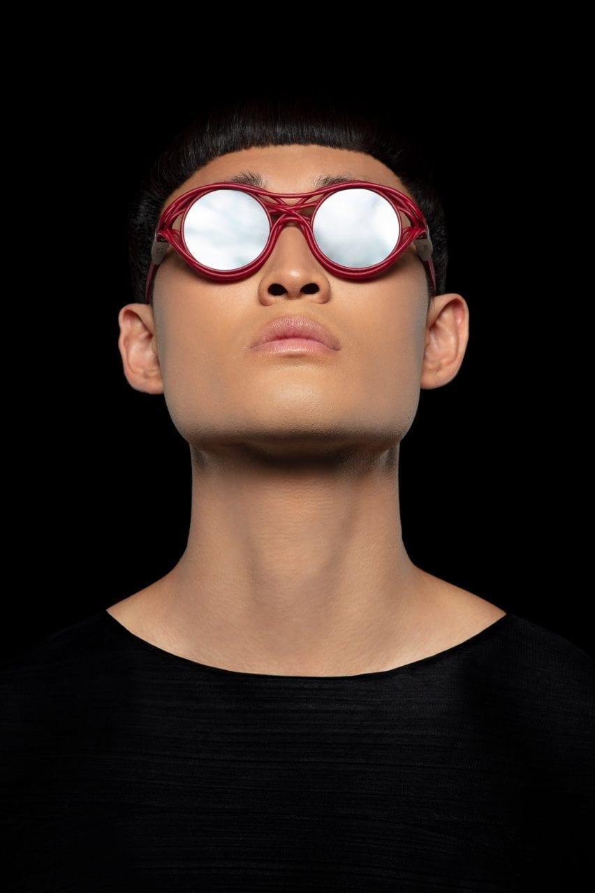 A man wearing a red pair of Kengo Kuma's sunglasses