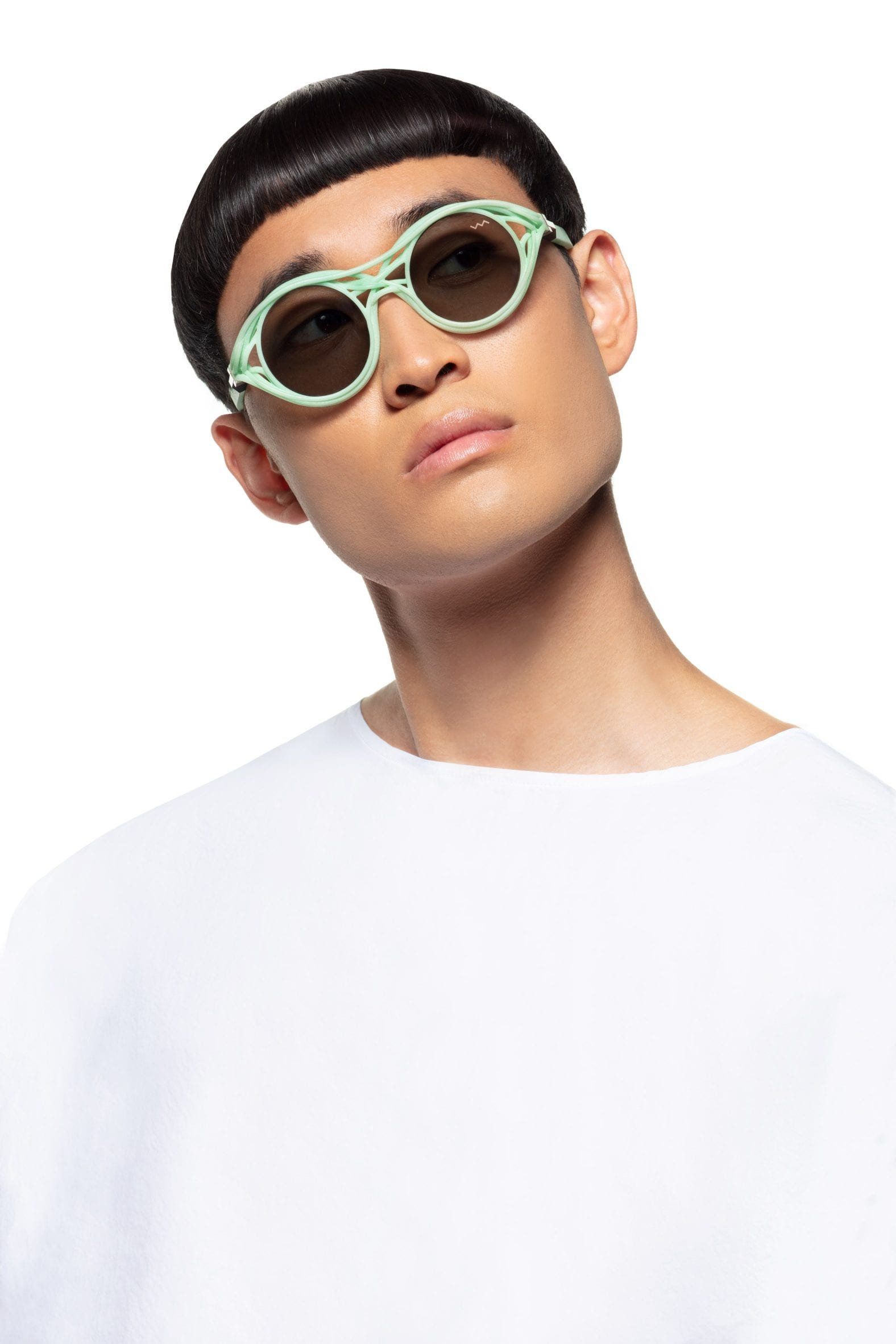 A man in a white top wears light green sunglasses