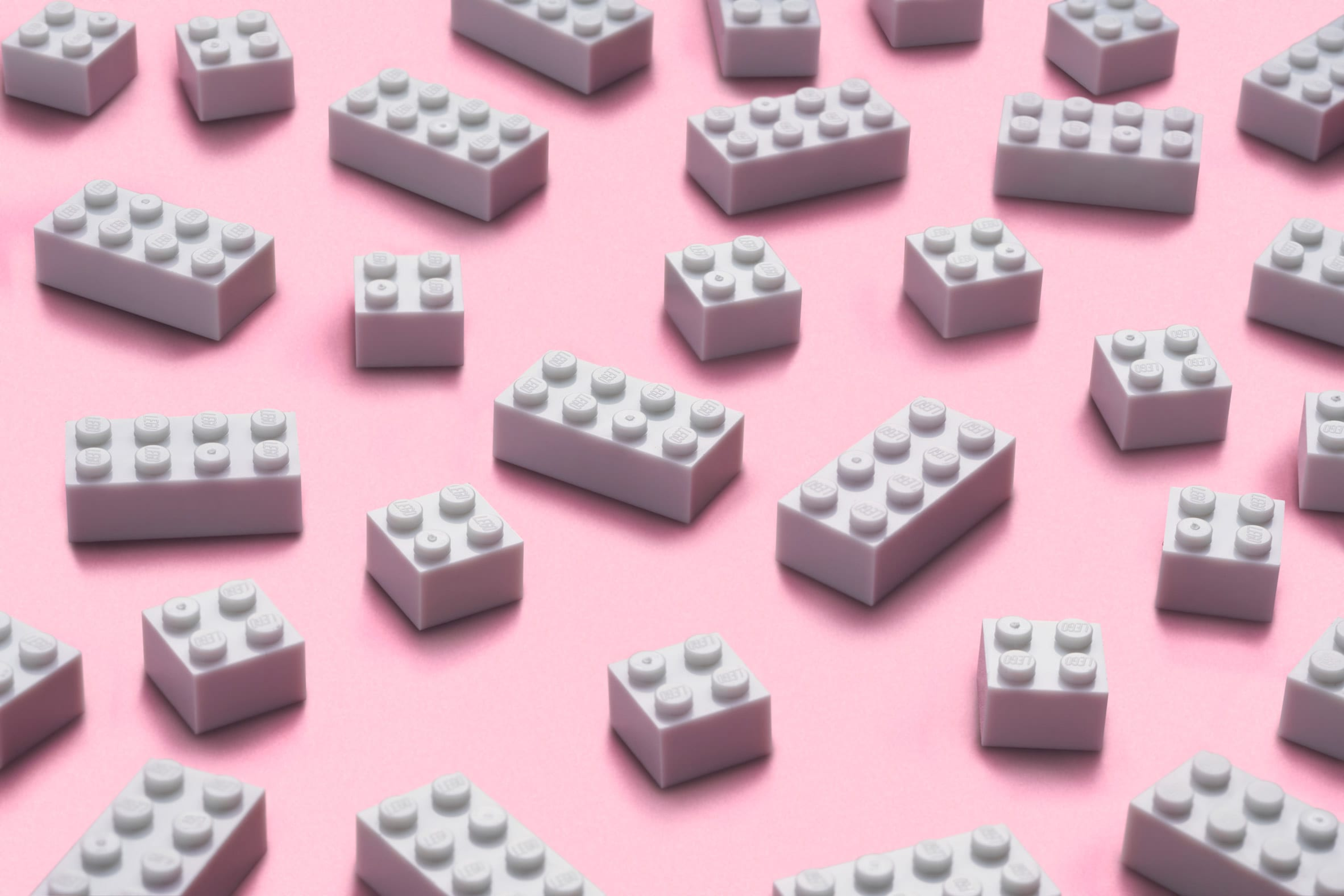 White 2x4 and 2x2 Lego bricks on a pink background