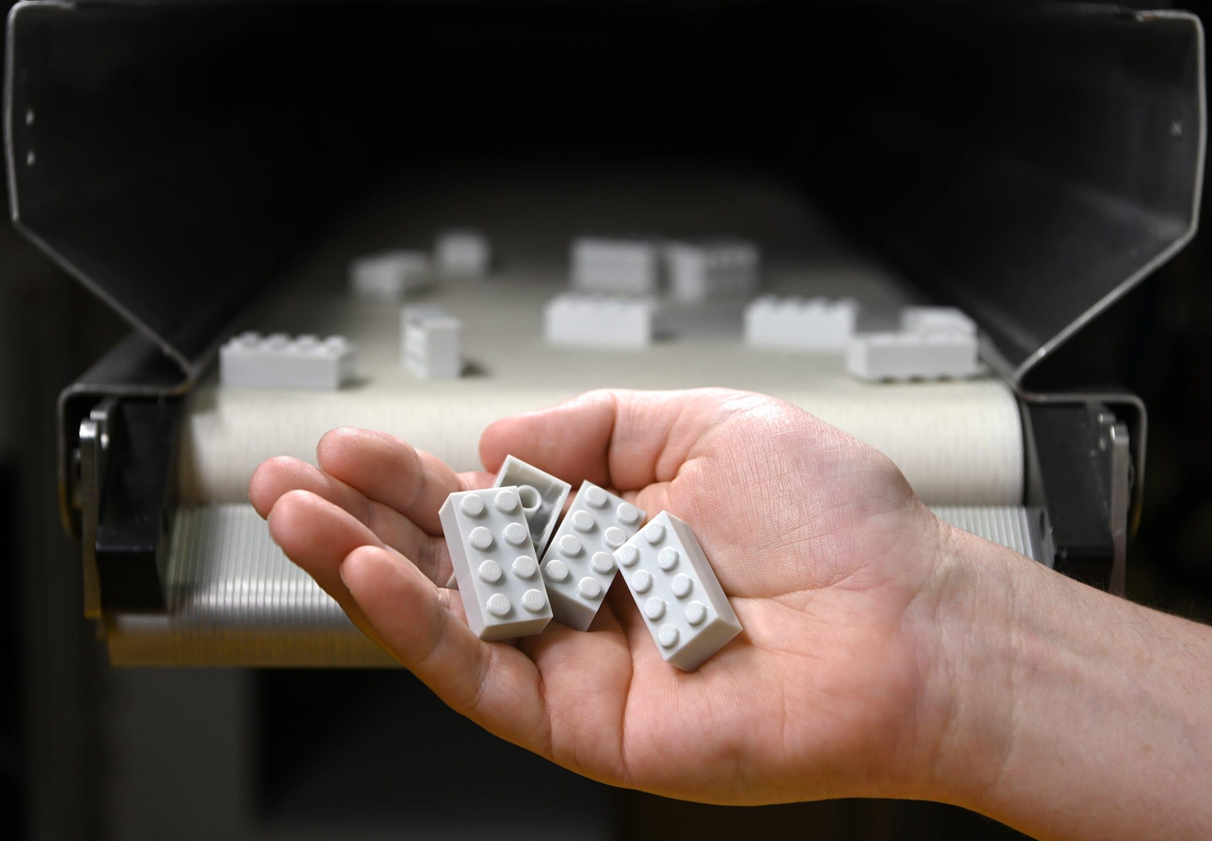 A hand holding 4 Lego bricks