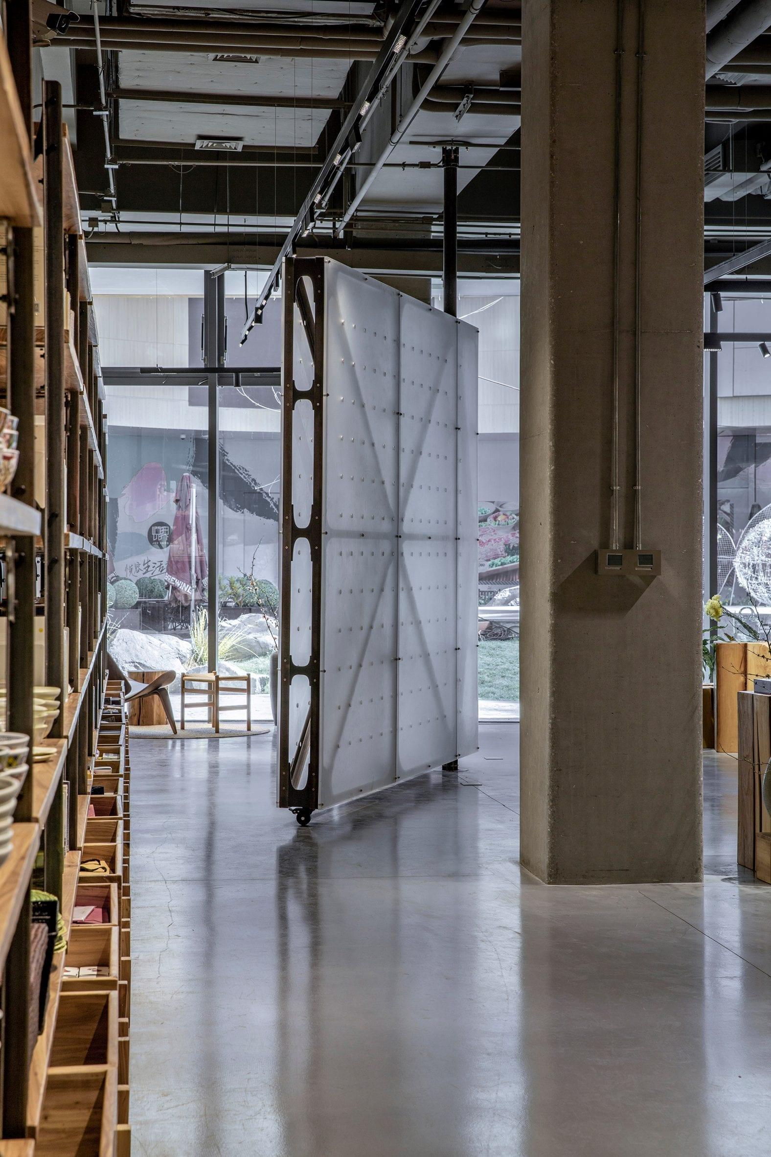 Translucent rotating wall on castors in Mumokuteki Concept Bookstore