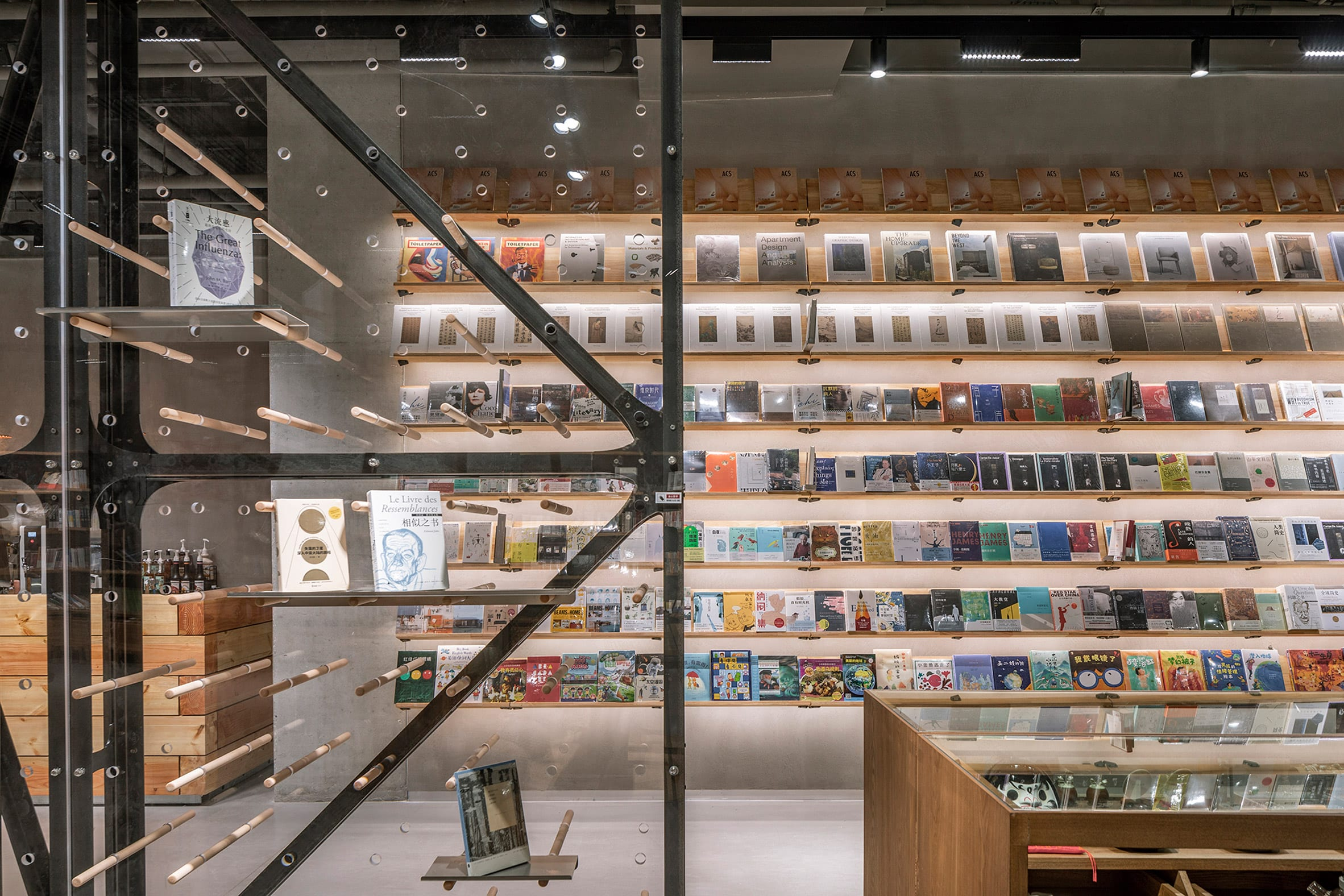 Illuminated shelving with books and clear divider with wooden dowels in retail interior by LUO Studio