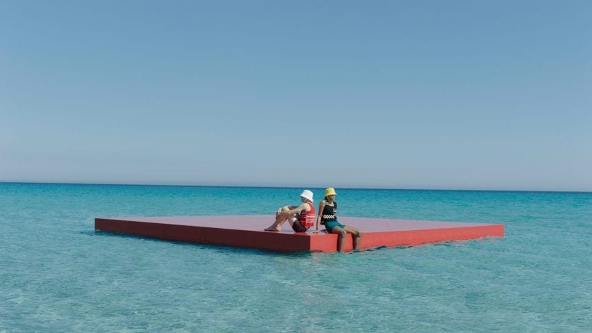 Two male models sit on a floating red plank