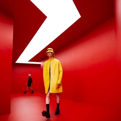 A man in a yellow coat walks through a red tunnel