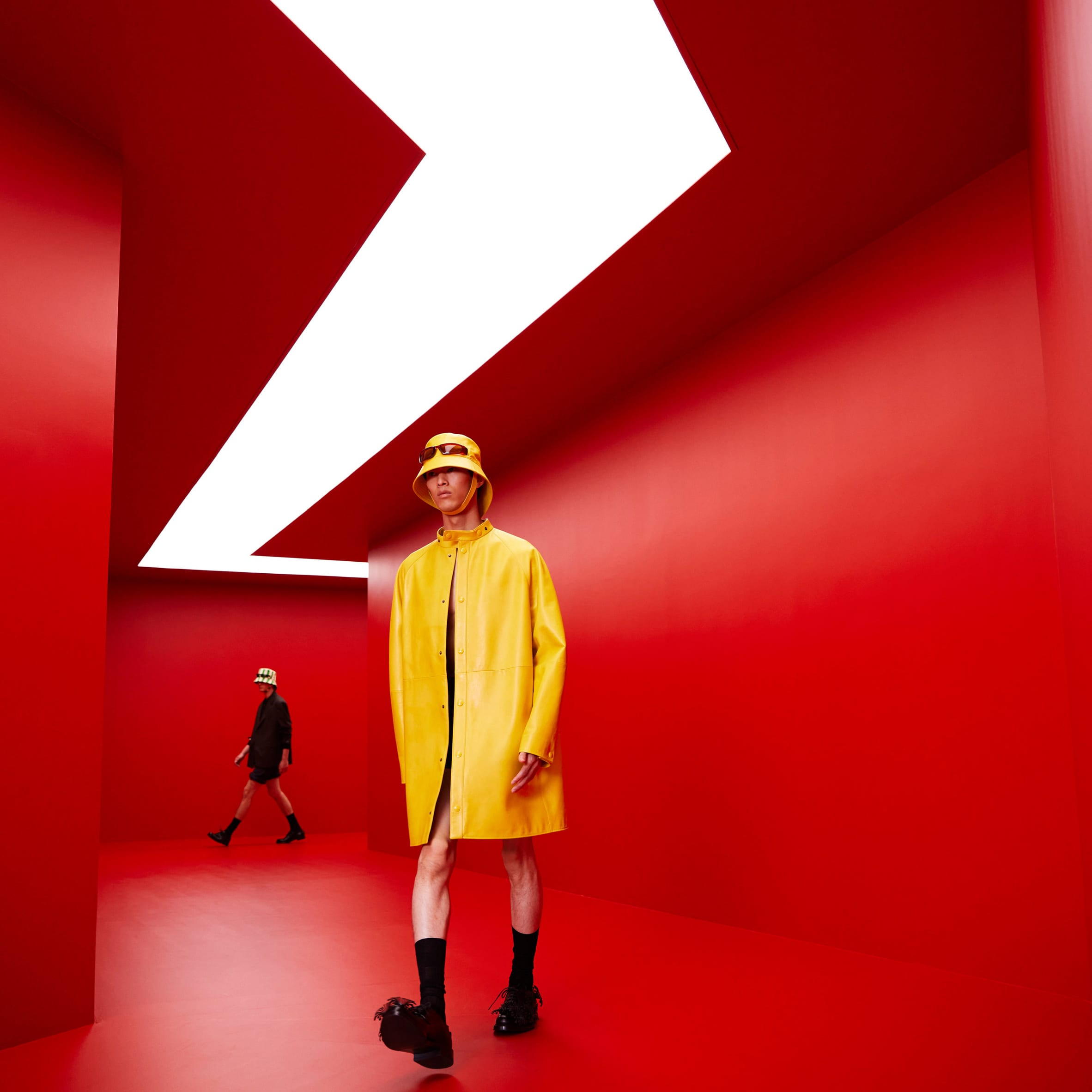 A model in a yellow coat walks through a red tunnel
