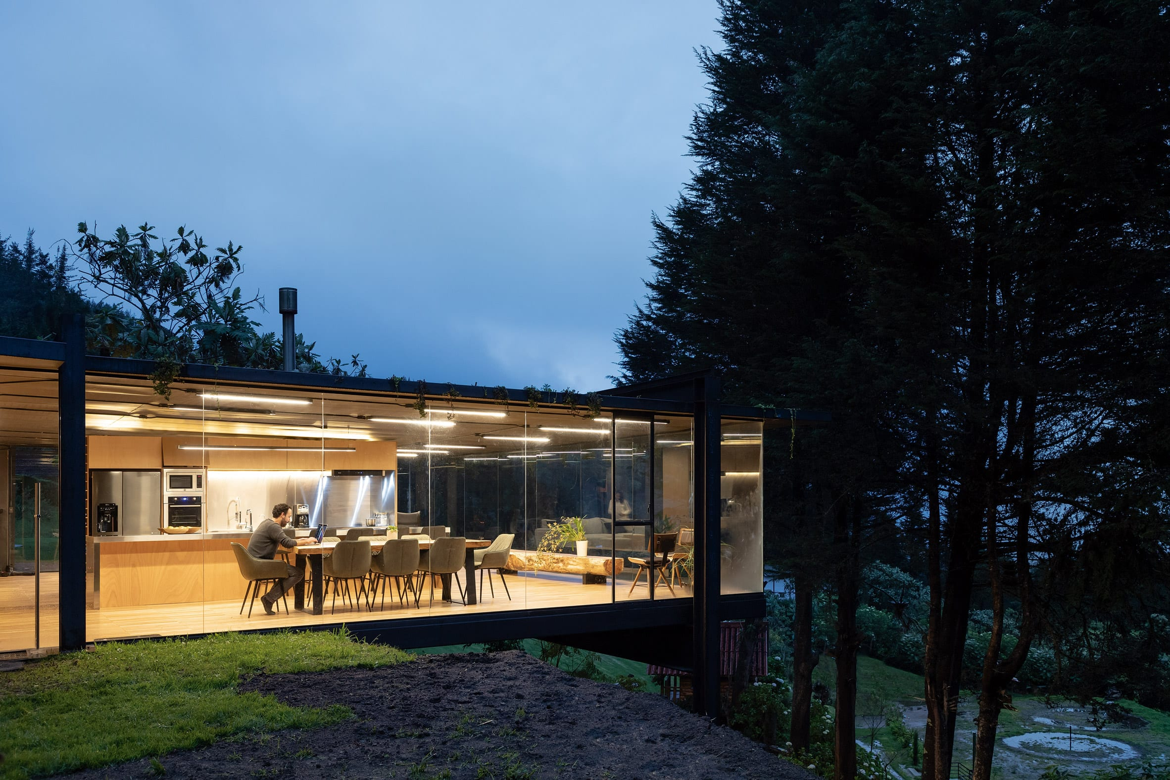 Rama Estudio has enlarged a small house in an Ecuadorian forest by adding a glass-and-metal box that extends over a hillside.