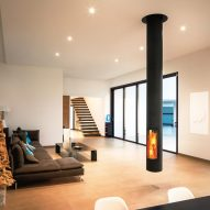 A living room with a suspended wood-burning fireplace