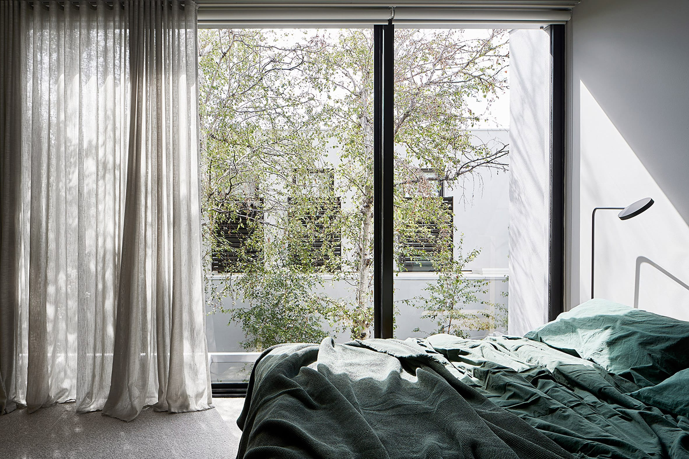 Bedroom with floor to ceiling windows and green bedding in Cunningham Street residence
