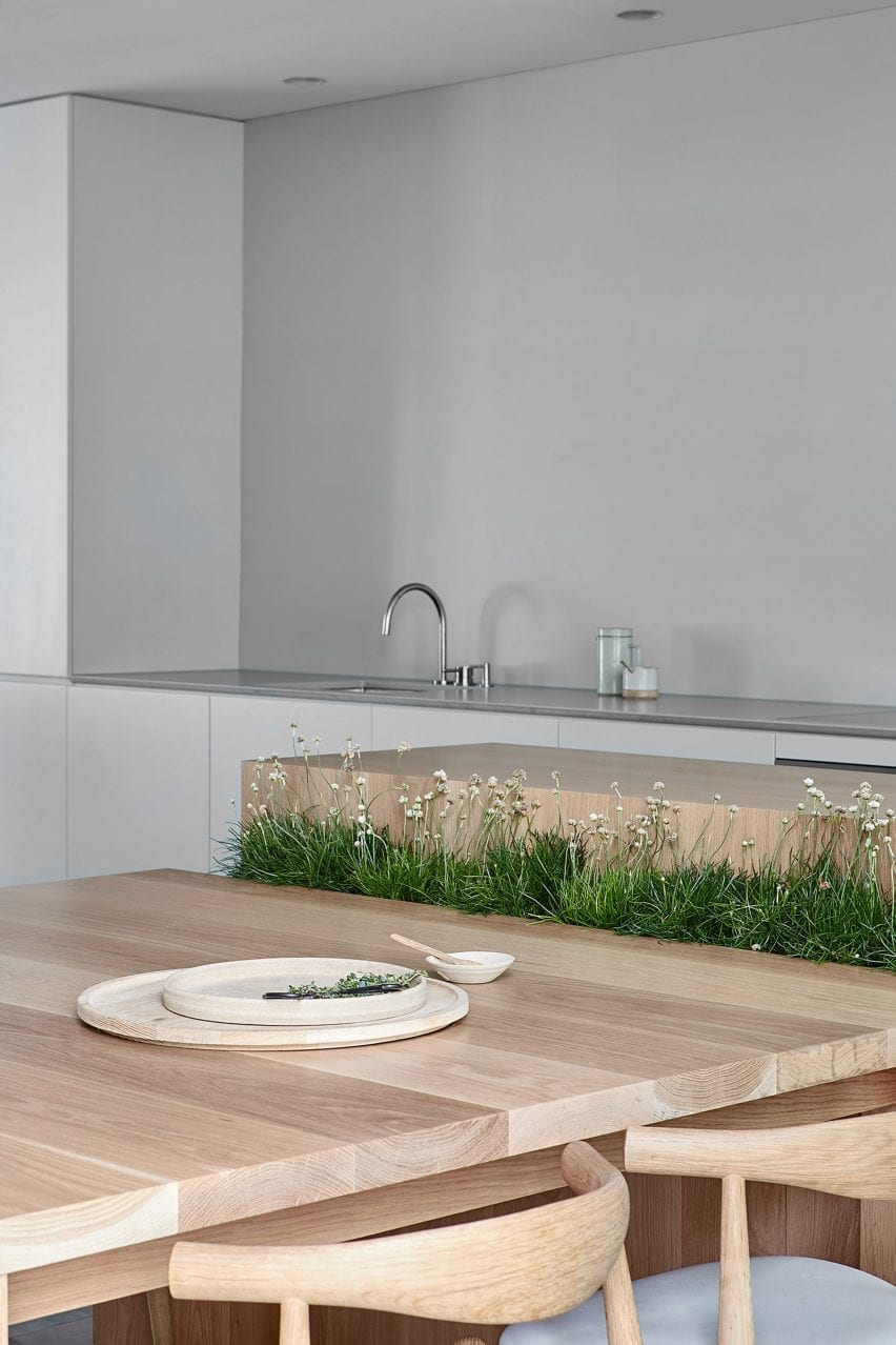 Wooden kitchen table setup with integrated planter in Cunningham Street residence