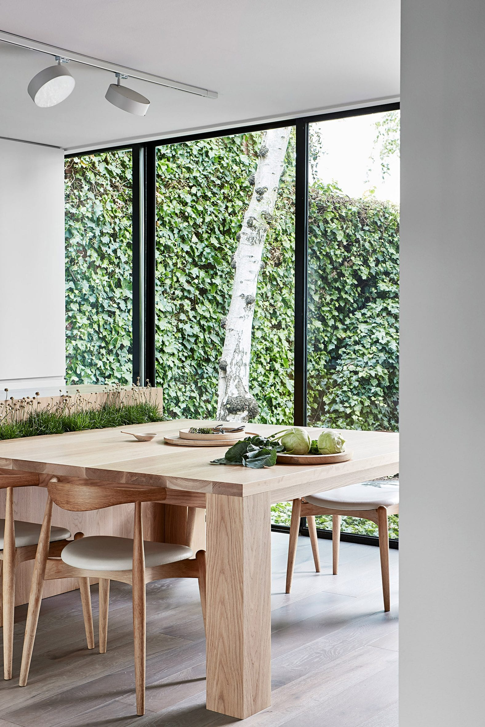 Kitchen interior Studio Four with wooden chairs and table and view of garden