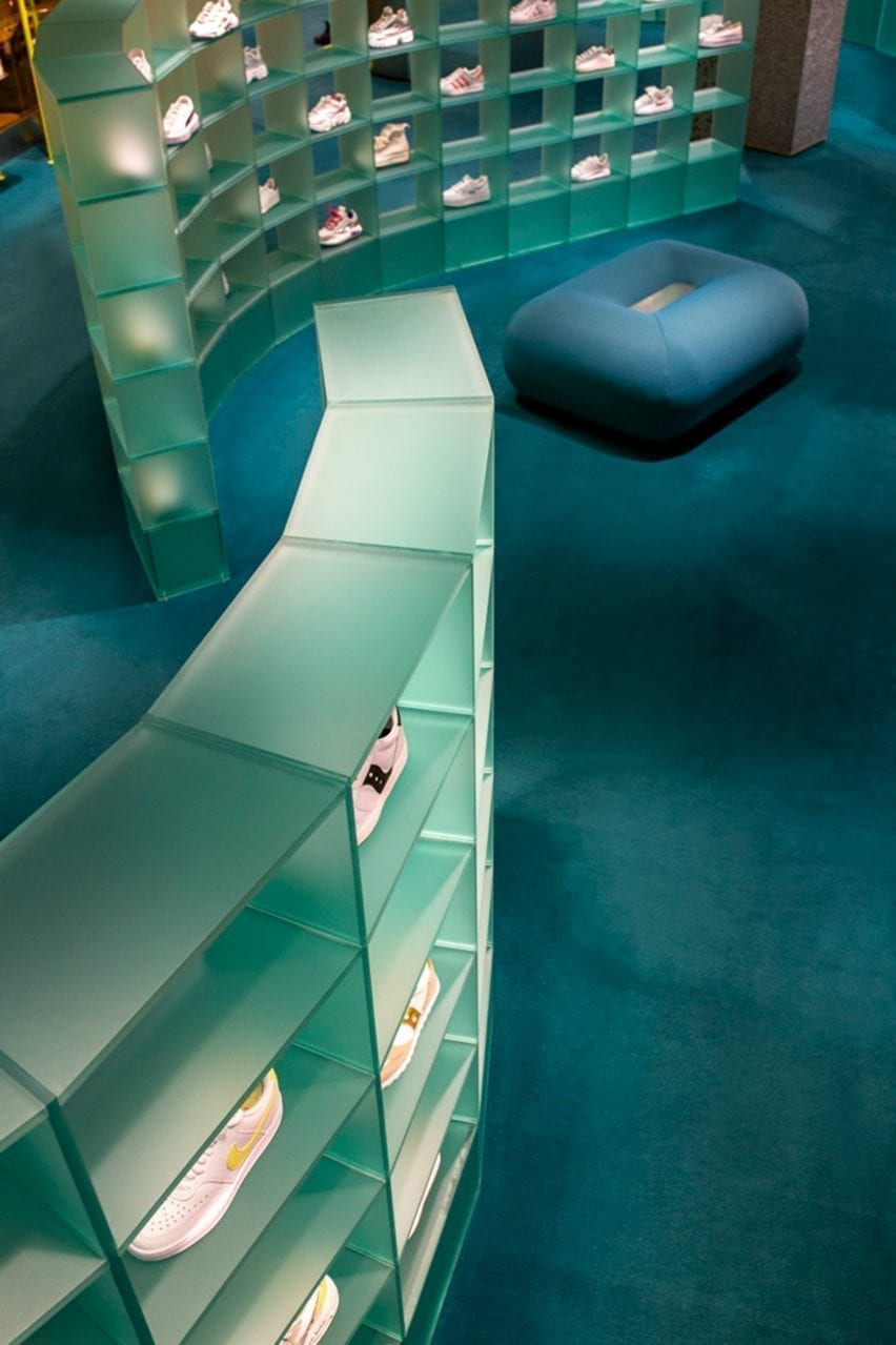 Curved plexiglass shelf with blue carpet trainers on display in Studiopepe's retail interior