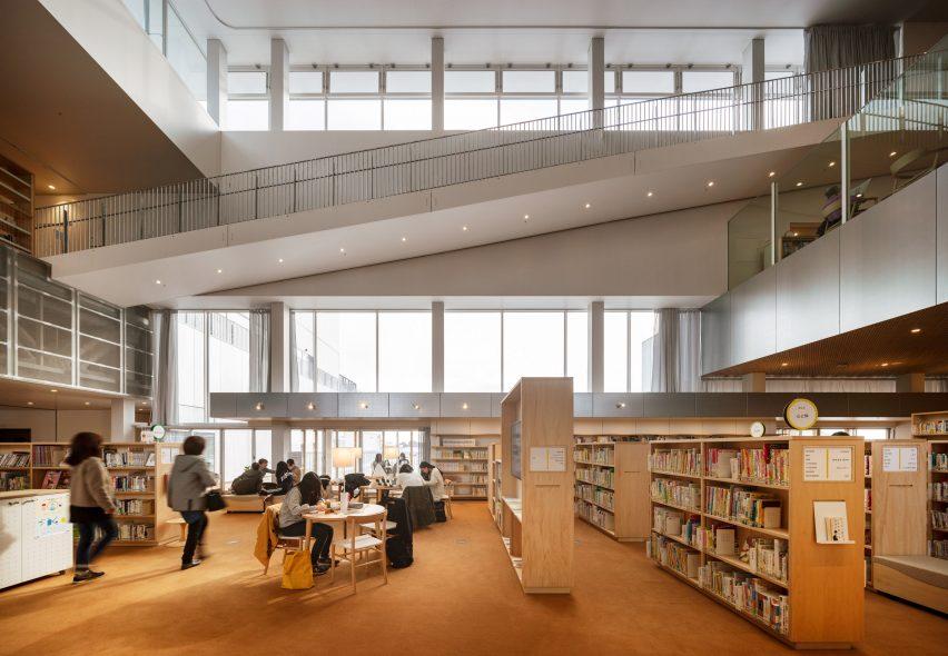 Karpet oranye menutupi lantai perpustakaan di Pusat Komunitas Sukagawa