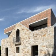 A brick extension extends above a stone wall