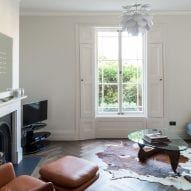 A living room has herringbone floors