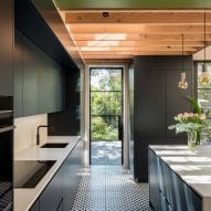 The dark cabinetry contrasts with white countertops