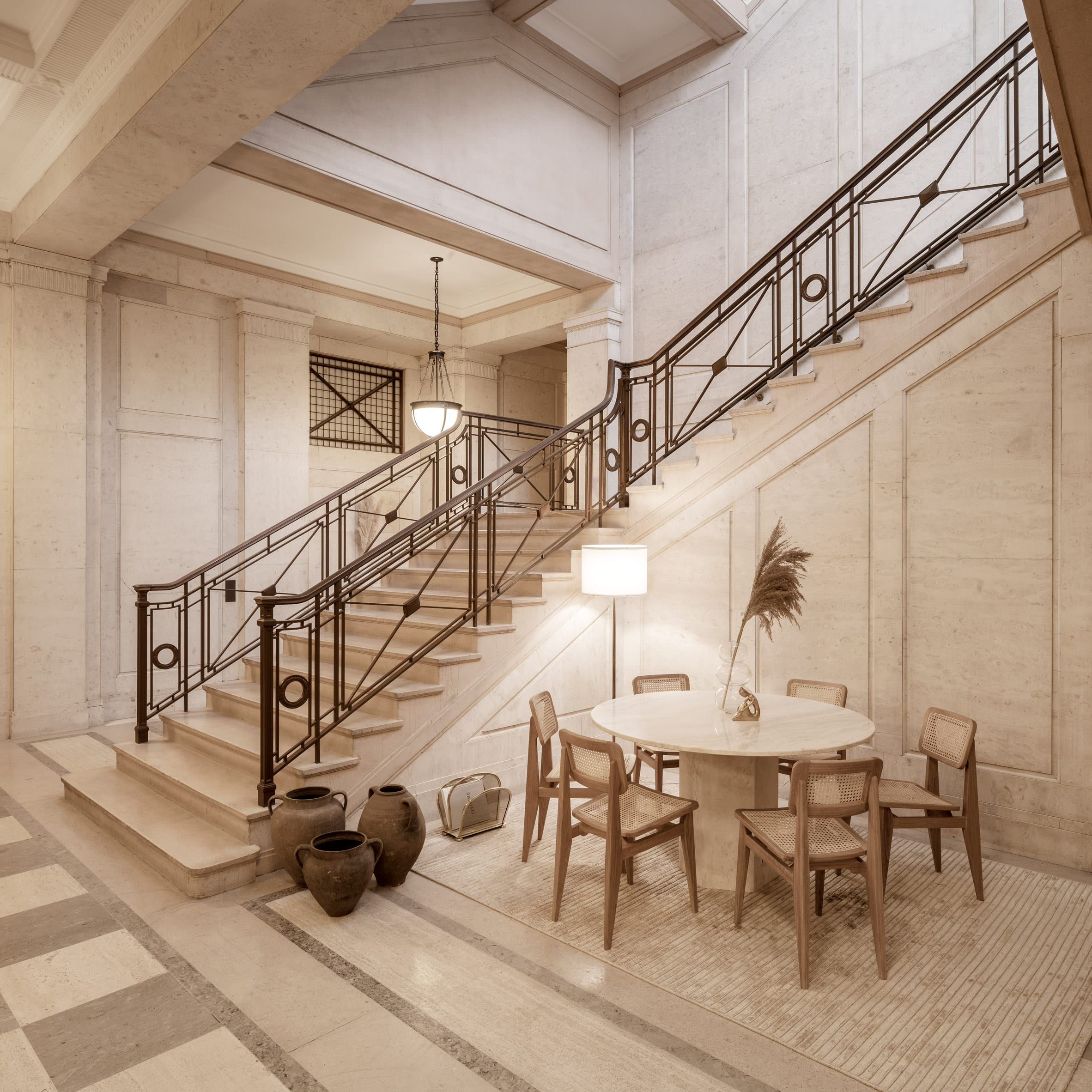Staircase of Victoria House with seating area of wooden chairs and marble table
