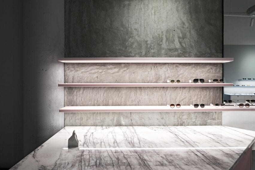 Transluscent pastel pink sunglasses displays with marble counter in retail interior by Studio Edwards