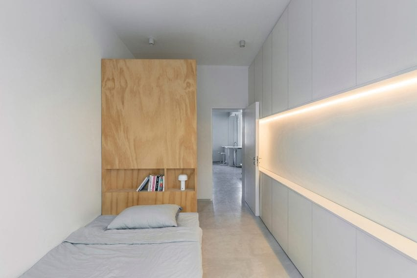 Bed with tall plywood backrest in white-painted room of post-war Beijing apartment