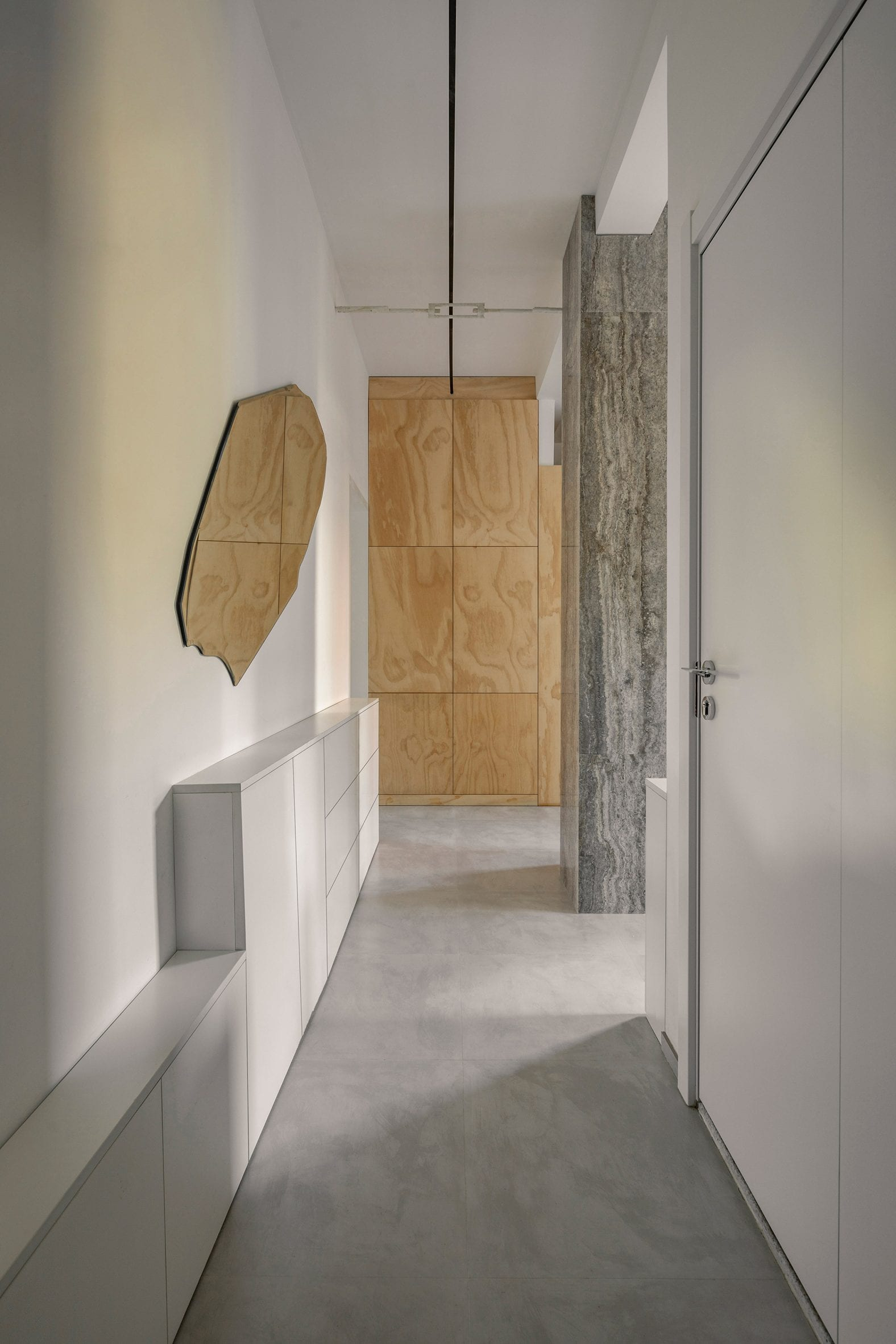Entryway with concrete floor, white walls and plywood joinery in post-war Beijing apartment