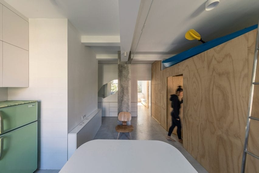 Open-plan room with kitchen and plywood unit holding a kayak in interior by Rooi