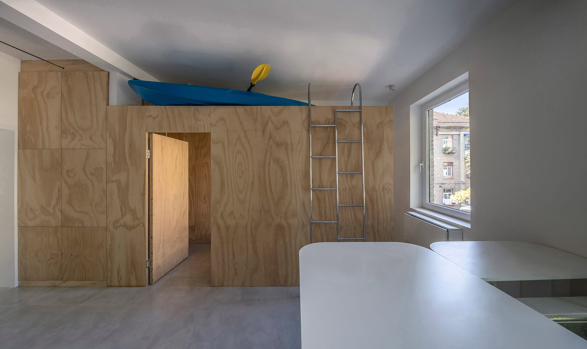 Modular plywood storage unit in apartment interior by Rooi