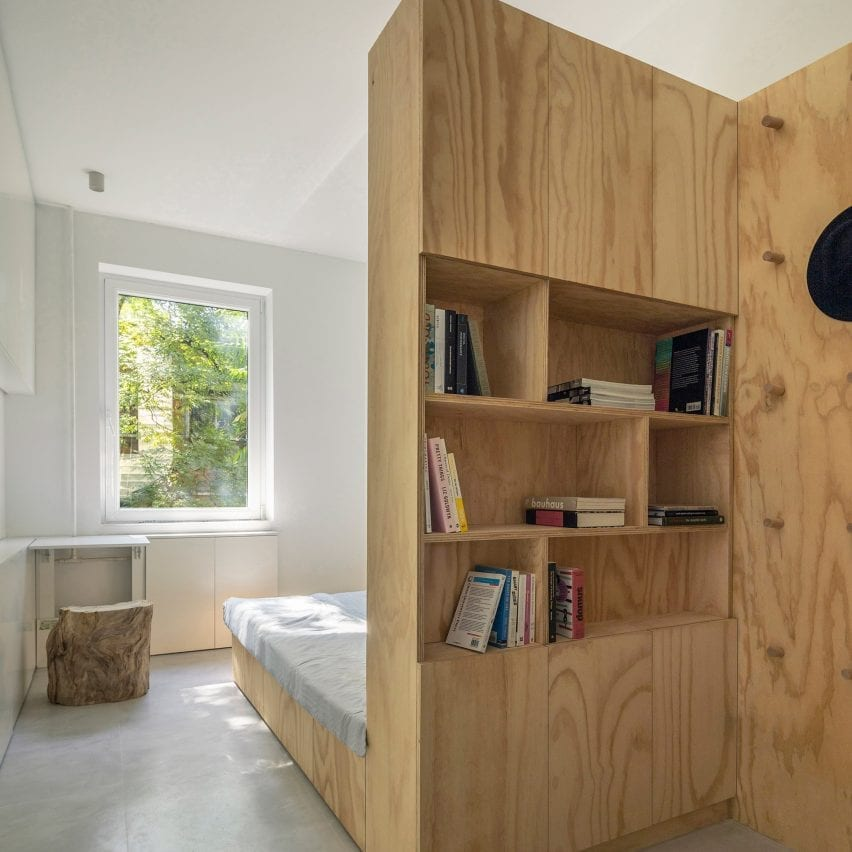 Bed with integrated bookcase in backrest in interior designed by Rooi