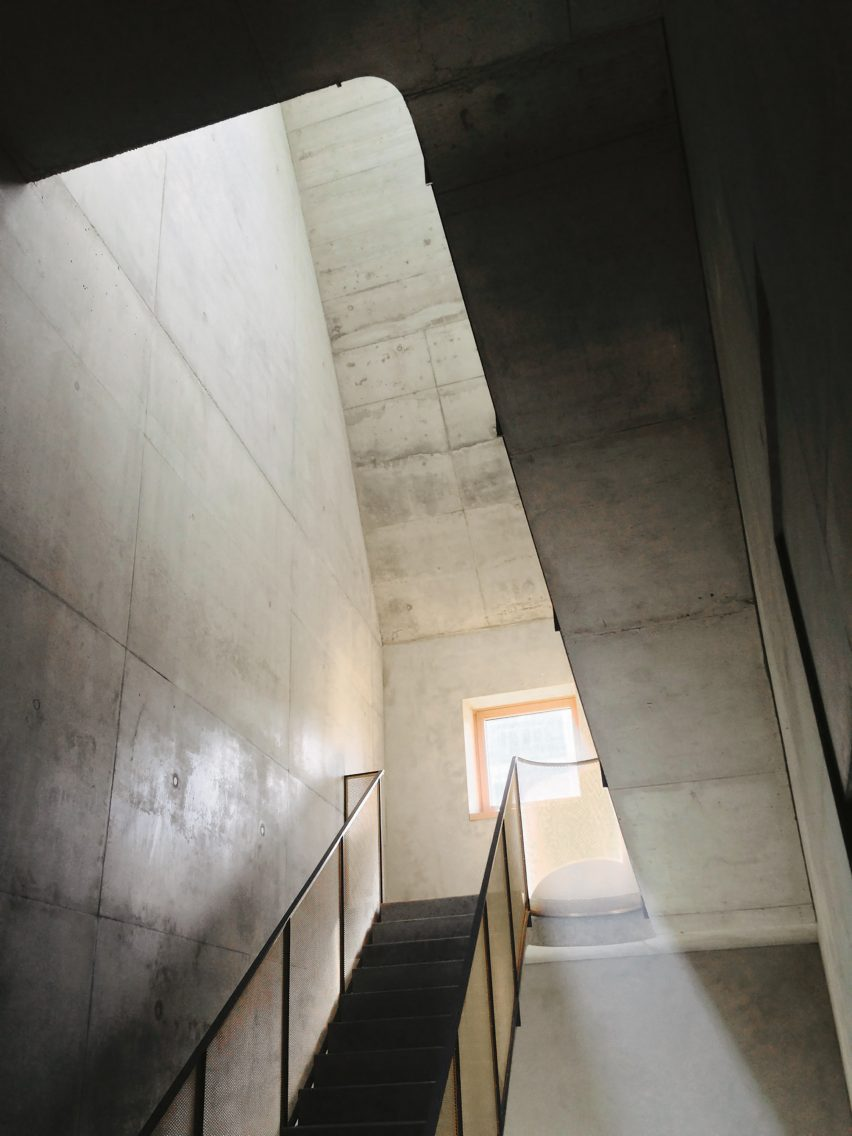 Concrete staircase with gold mesh railing in O12 residence