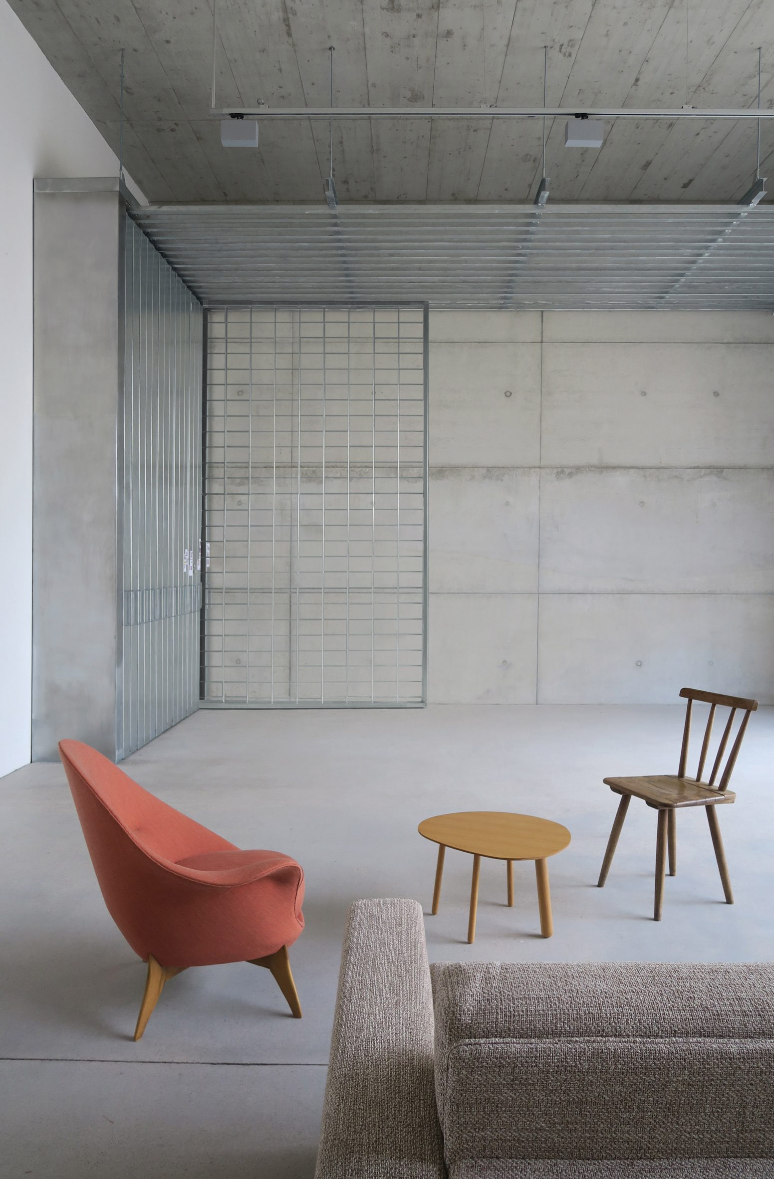 Concrete room with coral coloured armchair and wooden furnishings in Berlin home by Philipp von Matt