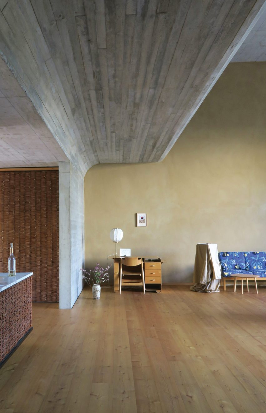 Room with curved concrete ceiling and wooden floors in O12 residence