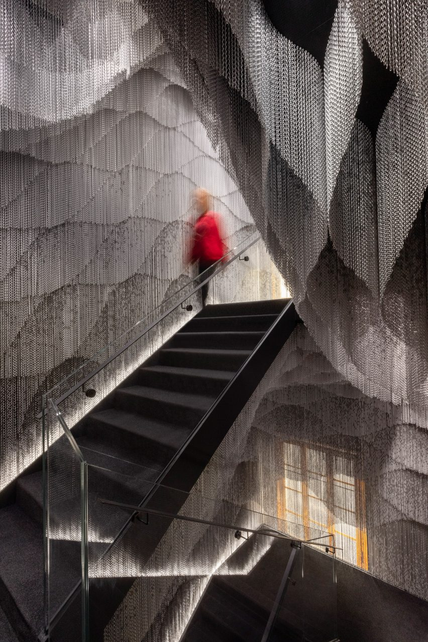 A staircase enclosed by a metal curtain