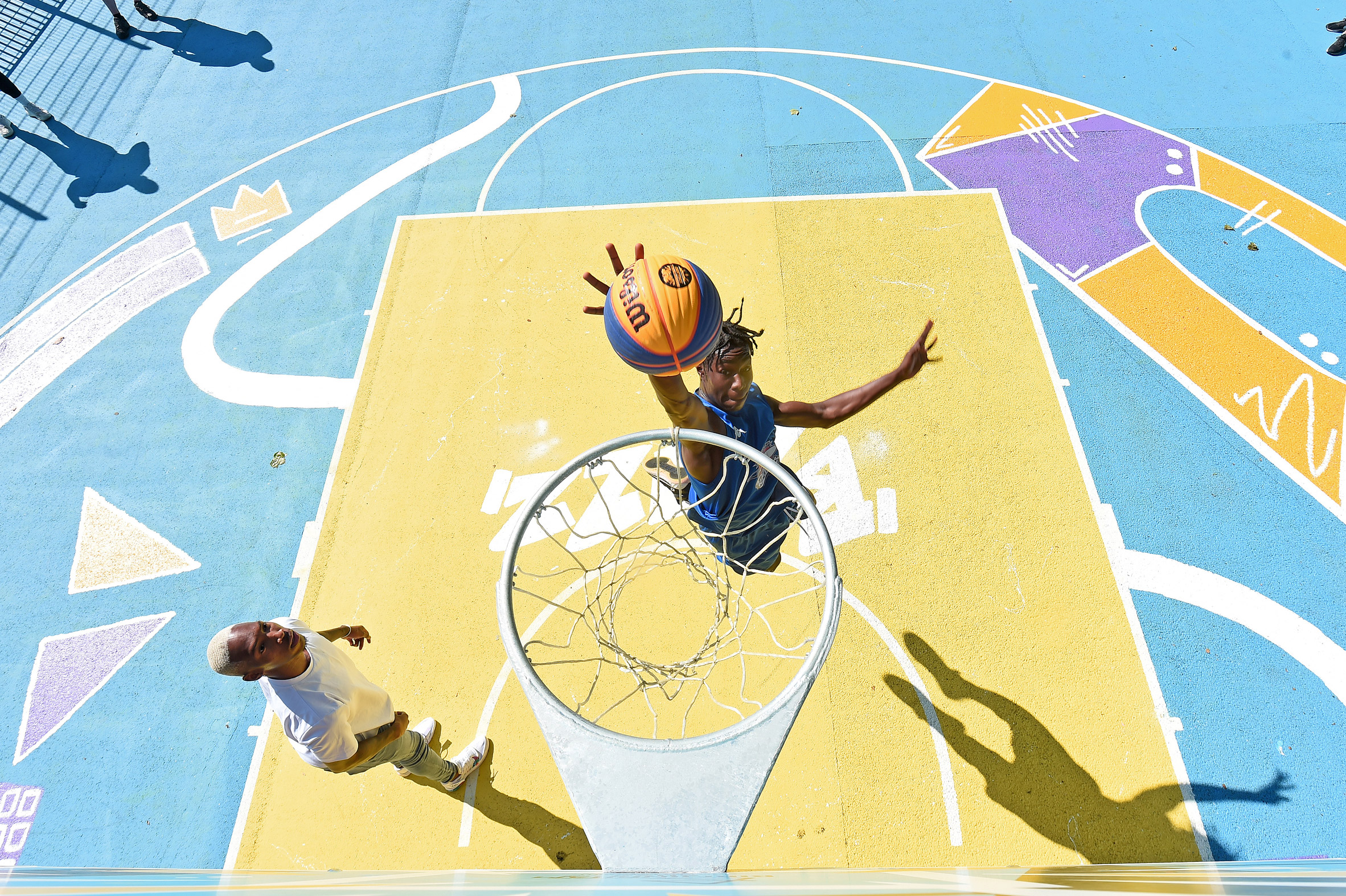 Two players play basketball on a colourful court