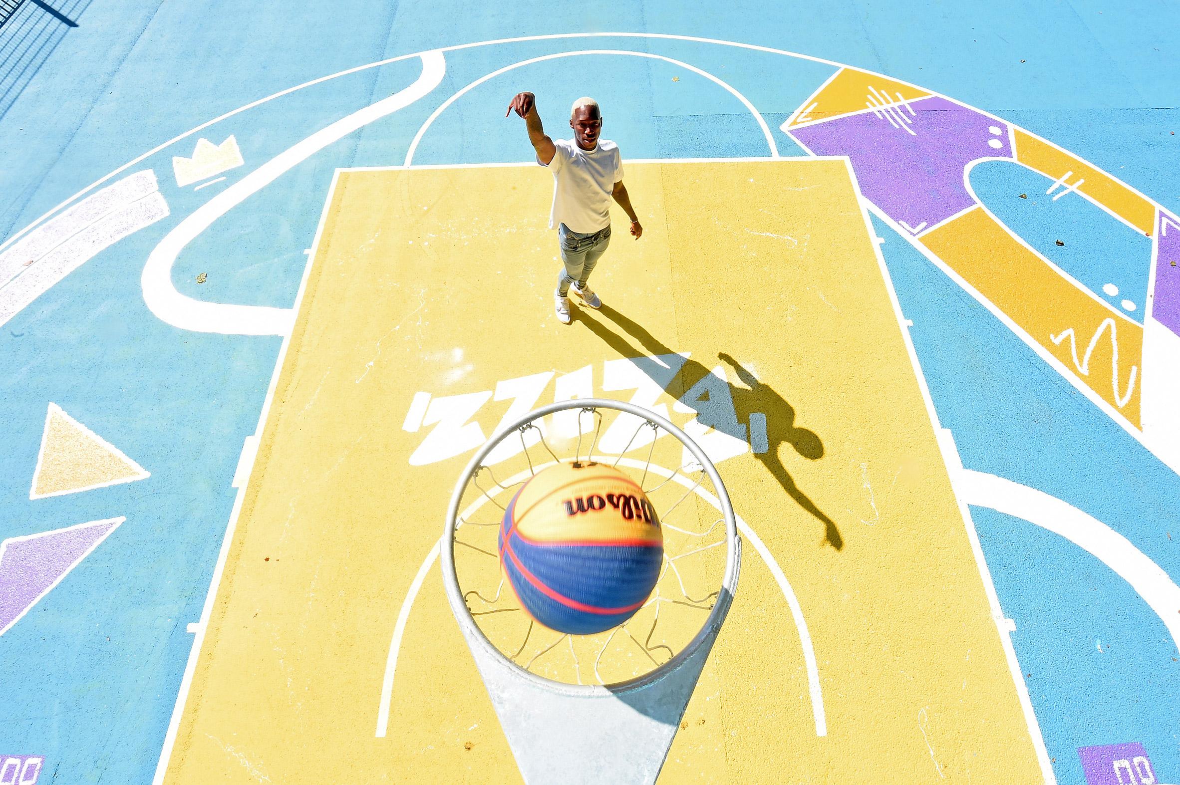 A player shoots a ball into a basketball hoop